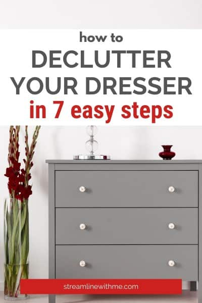 """Gray dresser with three drawers, bubble lamp, and a decorative container on top, green plant with dark red flowers on one side of it, with a text overlay that reads: """"How to declutter your dresser in 7 easy steps"""""""